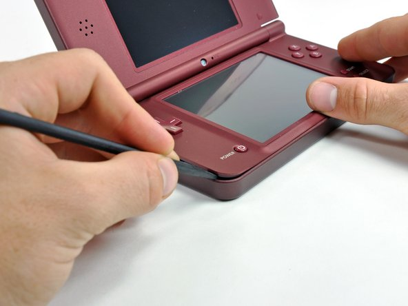 Image 1/3: Insert a spudger between the upper and lower case at the bottom left corner of the DSi.