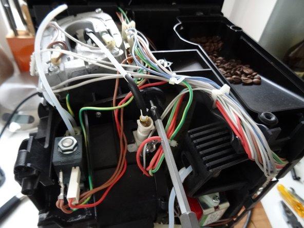 Boiler und Ventil sind mit drei Schrauben befestigt. Entferne auch die Kabel und einige Schläuche bis der Boiler sich lösen lässt.