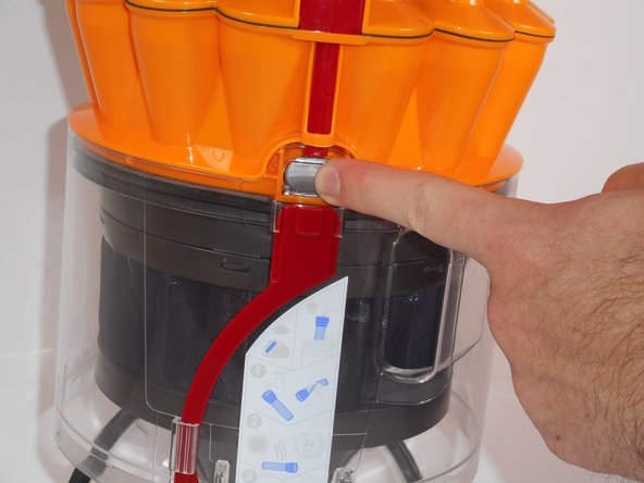 Push the grey button located in between the parts of the red lever to release the clear, bottom section of the bin.