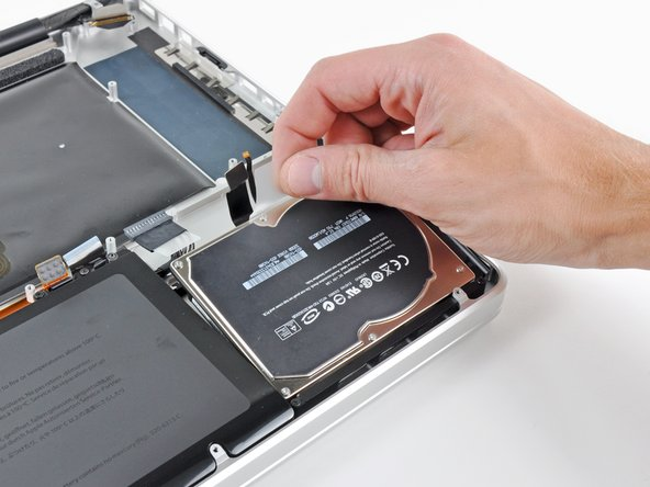 Using its attached pull tab, lift the hard drive out of the upper case.