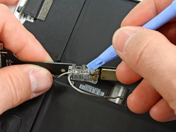 Carefully remove the plastic cover over the WiFi/Bluetooth board and dock connector cable using a plastic opening tool.