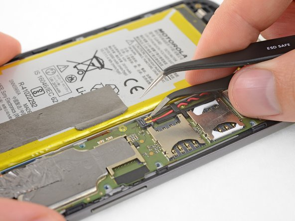 Insert a thin tool (such as one of your tweezer tips) under the red and black battery wires, and slide it underneath the battery connector.