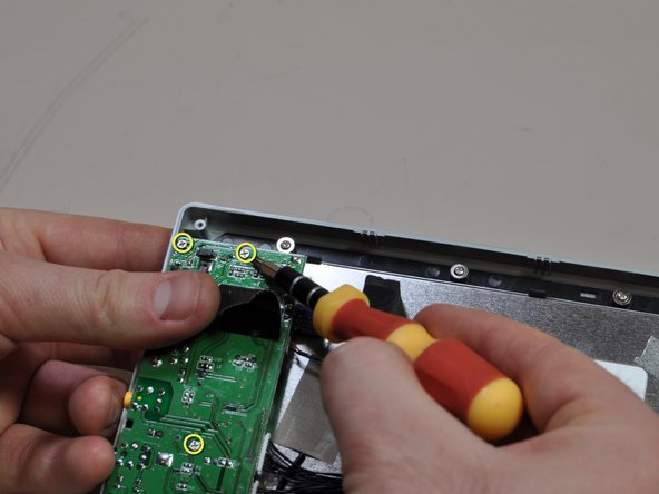 One of the screws is hidden below the black tape, so gently pull the tape to the side to gain access to it. Be sure to replace the tape when reinstalling the board.