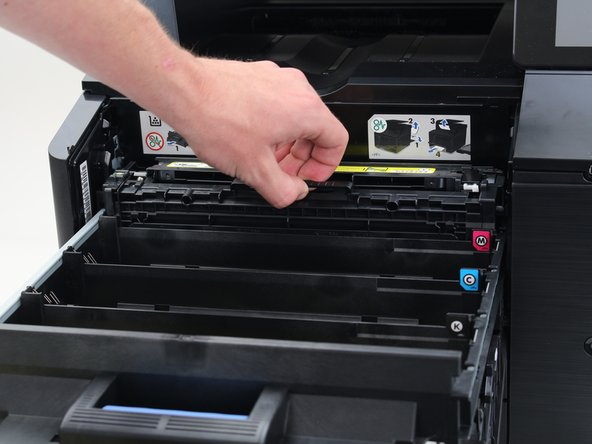 Use the handles built into the toner cartridges to remove them by pulling straight upwards.