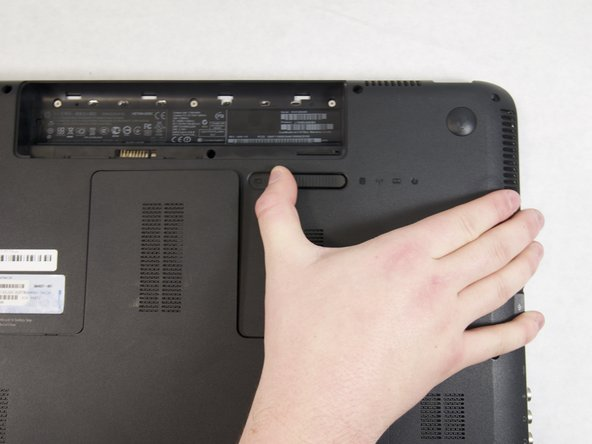 Flip over the laptop and push the sliding lock to the right (or whichever side indicates it with a symbol.)