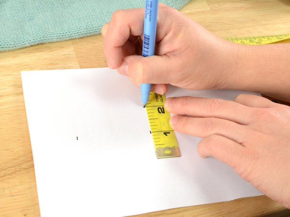 From the center, turn the measuring tape 90 degrees. Mark the endpoints of a line that measures the width of the hole, plus one inch.