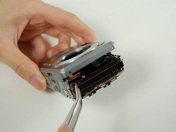 Gently pry apart the top casing using tweezers.