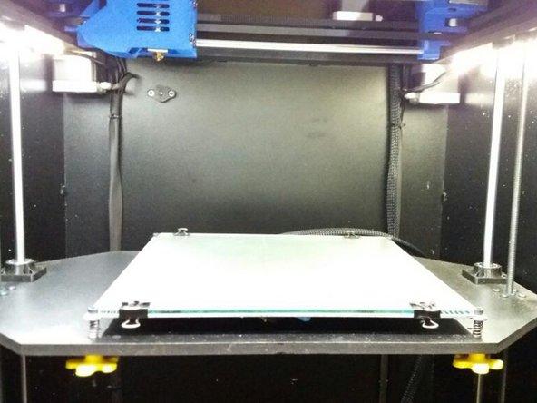Quando a mesa estiver na posição indicada pela foto pressione o botão de Reset do lado esquerdo da máquina, como indicado.