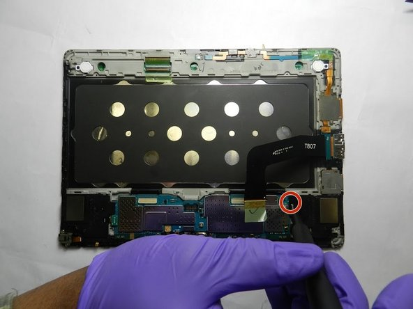 Use a Phillips #00 screwdriver to remove the screw holding the motherboard.