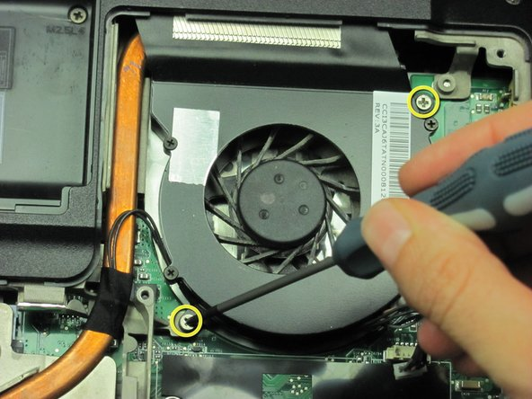 Remove the two screws located on opposite sides of the fan with a Phillips #00 screw driver.