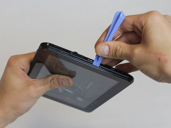 Squeeze the plastic opening tool in between the seam where the screen joins the plastic case.