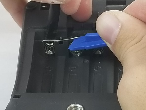 With the flat end of the black plastic spudger, pry the terminal away from the case.