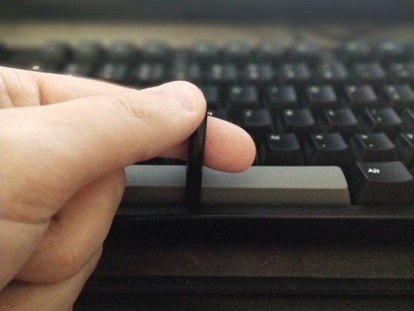 """Grab  the key cap removal tool, and while holding vertically, gently press down on the space bar until an audible """"click"""" is heard."""
