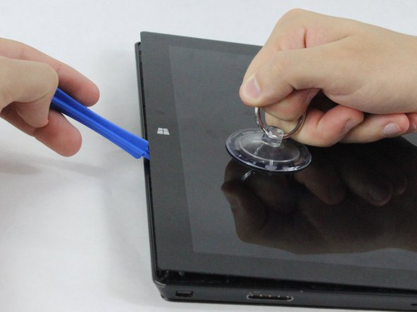 Using a plastic opening tool and a suction cup as needed for leverage, gently insert one edge of the opening tool under the corner of the screen.