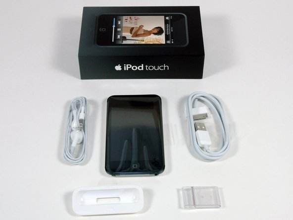 Inside the box: iPod Touch, headphones, USB cable, dock adapter, and cheap plastic stand.