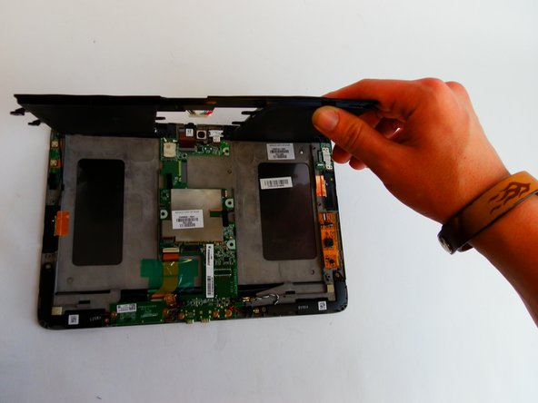 Lift the battery up by its edges and remove it carefully. There will be adhesive holding the battery down.