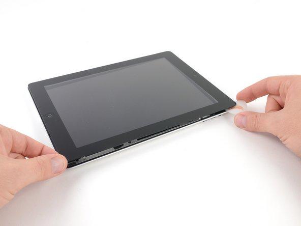 """Teilweise kann der Kleber rund um das iPad wieder angezogen haben.  Wenn das der Fall ist, fahre mit einem Pick unter die Kante des iPads, wo das Frontglas noch festklebt und """"durchtrenne"""" den Kleber."""