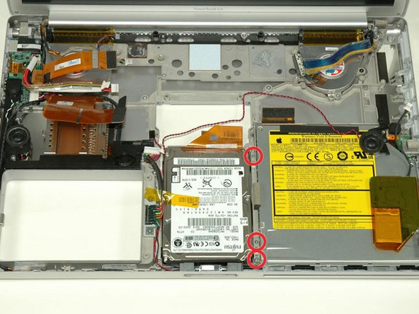 Remove the short black Phillips screw from the front right corner of the optical drive.