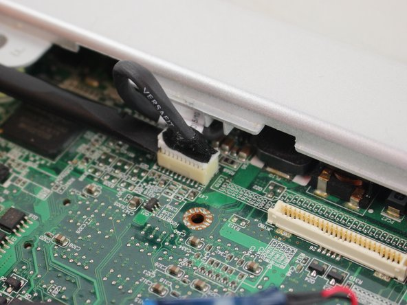 Image 2/2: Remove the trackpad ribbon cable from the motherboard using a spudger.