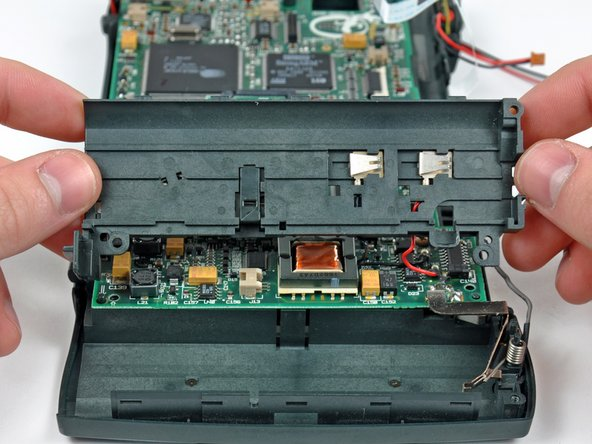 Lift the upper half of the battery compartment and gently lay it on the logic board.