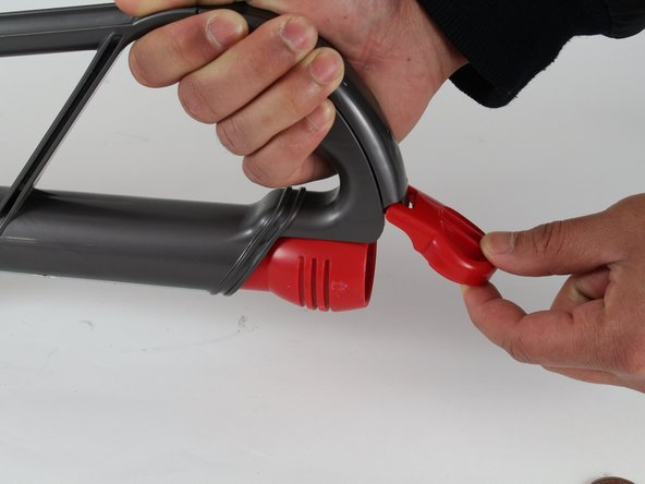 Place the vacuum either upright or on its back and lift the nozzle lid to access the nozzle.