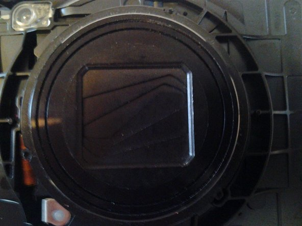 Once the front casing has been removed, this is what you will see. Get a q-tip, dip it in some rubbing alcohol or water, and begin to wipe away the residue, you can part the shutters and clean the lens as well.