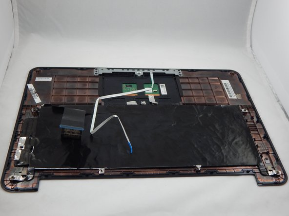 Remove the palm rest assembly from the bottom housing and lay it on a flat surface with the keyboard facing downward.