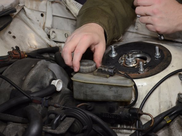 Twist the brake fluid reservoir cap counterclockwise and remove it.