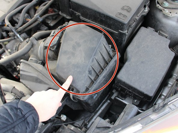 After opening the hood, locate the air filter container.