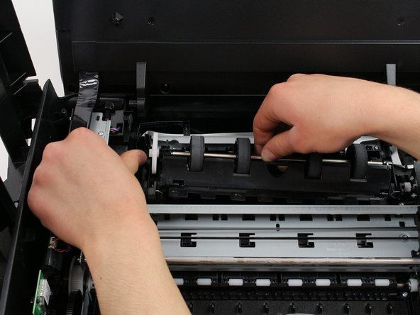 Pull the paper rollers up and out of your HP printer with one hand while the other continues to depress the lever away from the paper rollers.