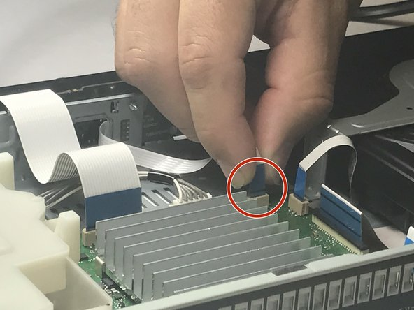 Now, pull the small ribbon cable that connects between the motherboard and the Bluetooth module.
