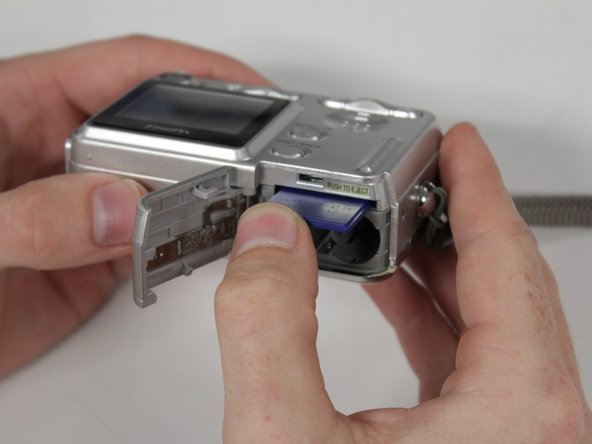 Image 2/3: The memory card is spring-loaded and will pop out of the camera far enough to be removed by hand.