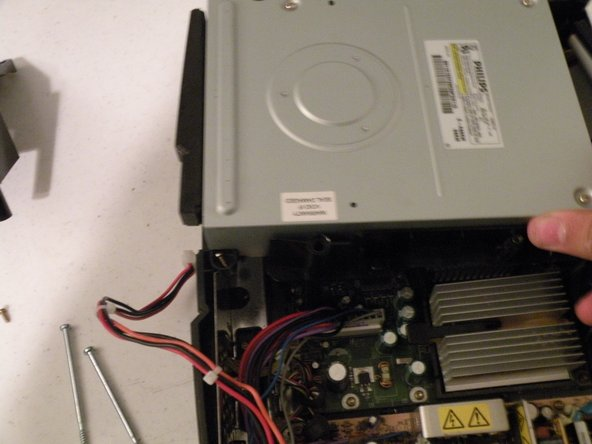 Lift the DVD-ROM drive and the plastic attatched to it out. This reveals the logic board.