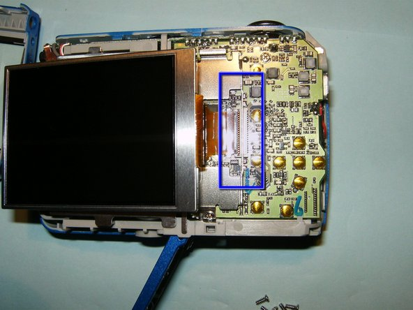 Carefully slide the LCD out of its holder until the connector, highlighted in blue, is visible. Open the clip on the connector by pulling it with your fingernail to the right of the screen.