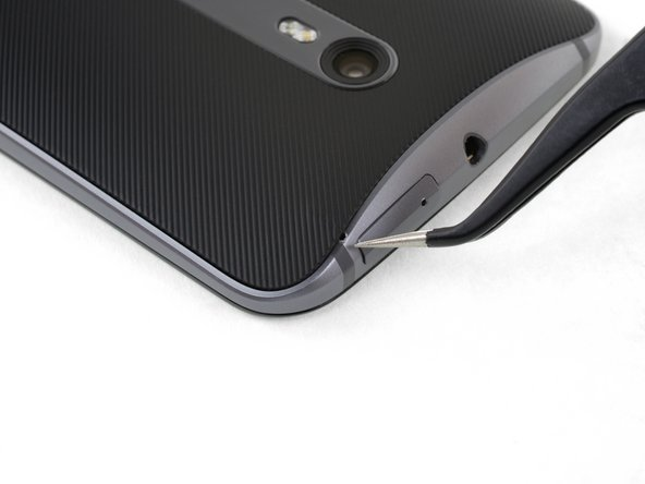 Hold a pair of pointed tweezers closed, and insert them into the small hole on the edge of the back cover near the SIM card slot.