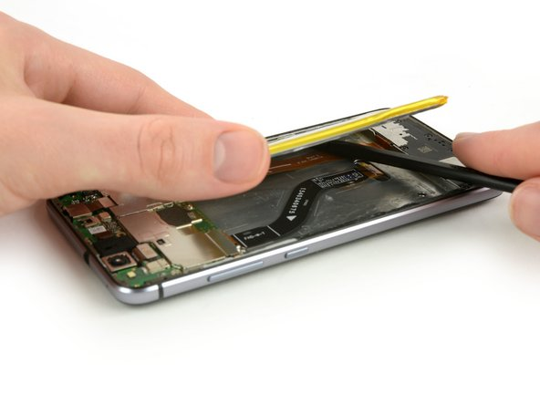 Use a spudger to cut the rest of the adhesive and lever the battery out of the phone.
