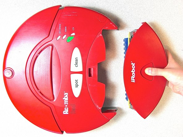Image 2/2: While holding in the button, slide the back piece away from the main body of the Roomba.