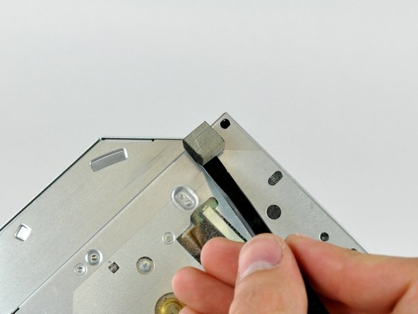 Use the flat end of a spudger to remove the small piece of EMI foam from the underside of the optical drive.