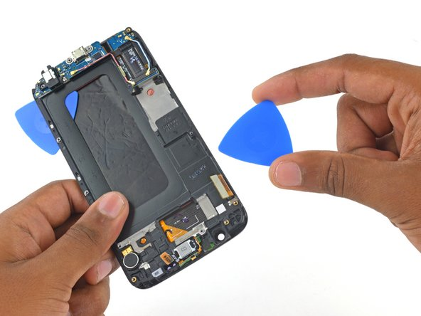 Image 1/3: Insert a second opening pick between the frame and display assembly on the display cable side of the phone.