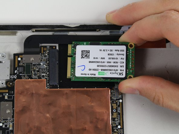 Lift up and pull gently on the SSD to remove it from the black connector.