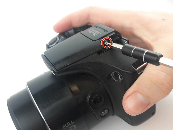 Remove the two screws (5-6mm) on the left and right side of the shutter panel  with a Phillips PH000 screwdriver.