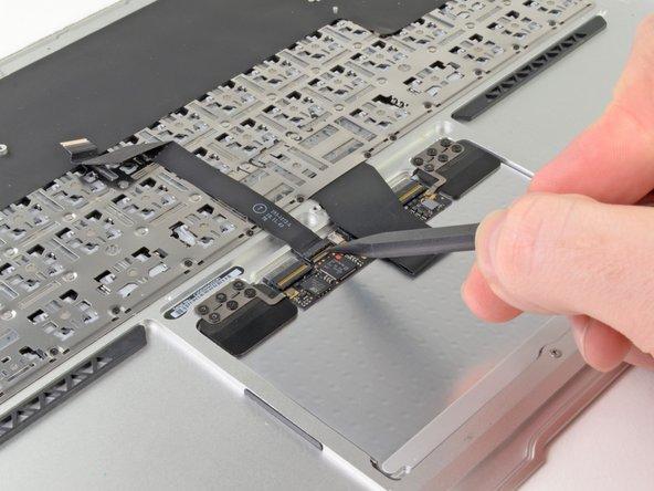 Klappe den Sicherungsbügel am ZIF Anschluss des Flachbandkabels zum Trackpad mit der Spudgerspitze oder deinem Fingernagel hoch.