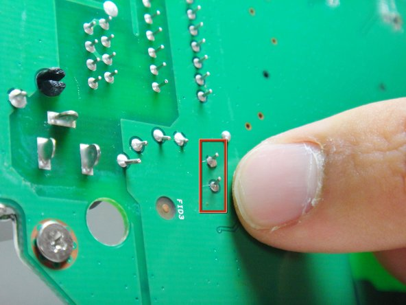Locate the two soldered contacts of the capacitor.
