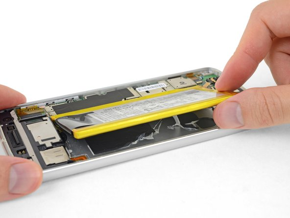Continue pulling up the battery until all the adhesive releases from the rear case.