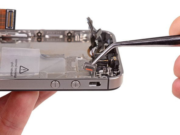 Use a pair of tweezers to remove the silent switch from the case of the iPhone.