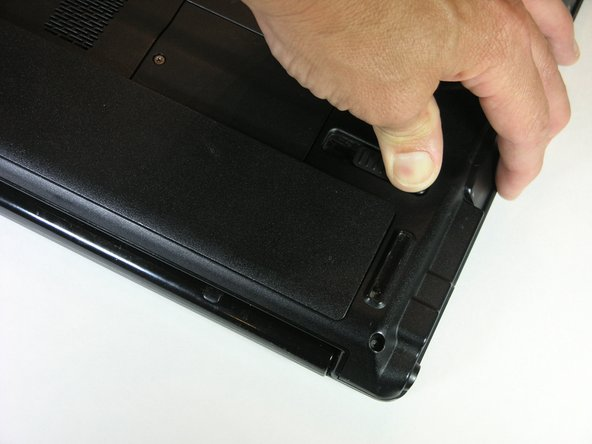 The battery will be lifted out of the laptop slightly as you press the latch over as far as it will go.