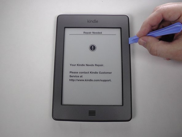 Use a plastic opening tool to pry the top three sides of the bezel. Since there is glue under the bezel,  gently pivot the face at the bottom off the Kindle and slide the clips out.