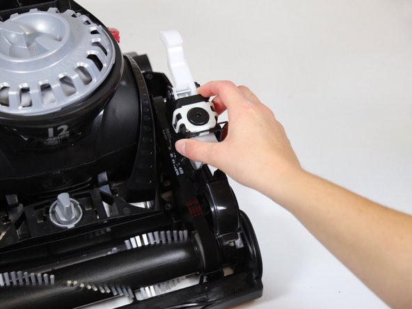 Lift up on the belt latch assembly and remove it from the vacuum.