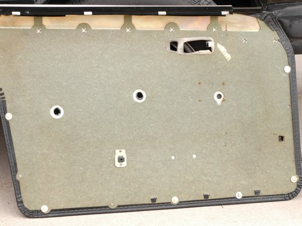 Pictured is the back of your door panel once removed. Notice the white plastic clips around the edge. Notice that many are missing. There should be several more on this door. Also, notice that some are broken.