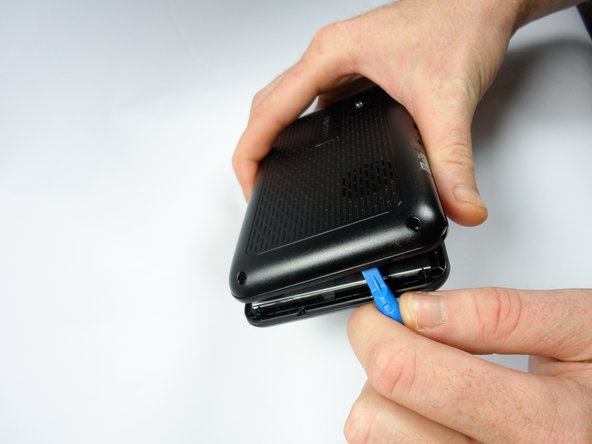 Gently use the two blue plastic opening tools from the 70 piece iFixit Pro Tech Tool Kit to open the GPS unit.